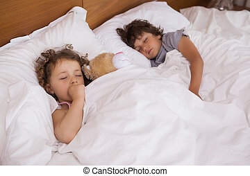 Young girl and boy sleeping in bed