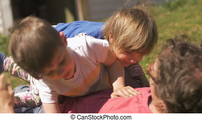 Young girl and boy wrestling and laying on their father in...