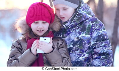 young girl and boy writes on the phone