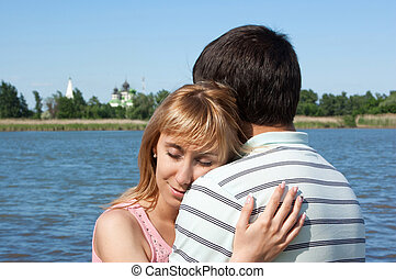 young beautiful couple walks along the river bank