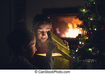 Young girl and toddler boy opening a golden giftbox under Christmas tree