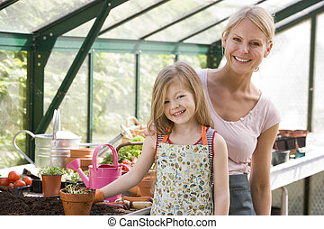 Young girl and woman in greenhouse smiling