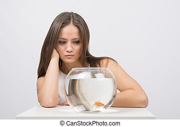 Young girl angrily looking at goldfish in a fishbowl
