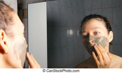 Young girl applying a cosmetic mask of blue clay in the bathroom, 4K.