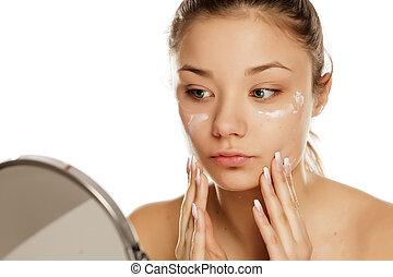 young girl applying face cream
