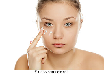 young girl applying face cream