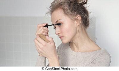 Young girl applying mascara - Young pretty girl applying...
