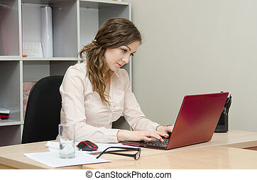 Young girl at a laptop in the office