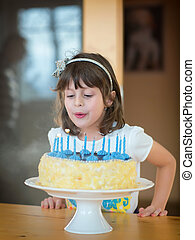 Young girl at birthday party - Girl how to blows candles on...