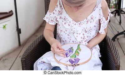 young girl at cafe sewing with needle. needlework, ...