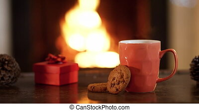 Close up of the hand of a young mixed race girl reaching and taking a cookie from the table in her sitting room at Christmas time, a mug and a small red gift box are also on the table and the flickering flames of an open fire in a fireplace are in the background