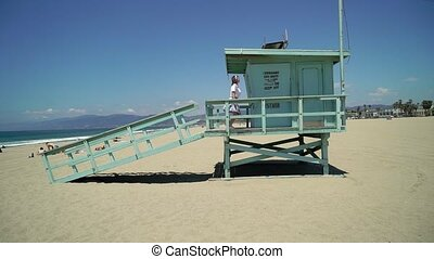 Young girl at the beach. Lifeguard booth
