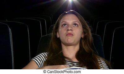 young girl at the cinema. eating popcorn. Close up