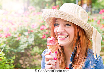Young girl at the park eating an ice cream