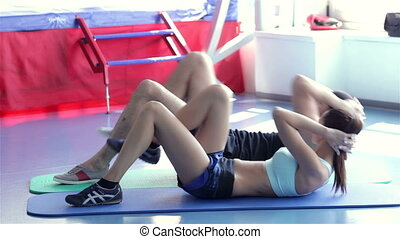 Young girl athlete and her trainer doing exercise for the abs