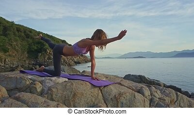 Young Girl Balances Holding Yoga Pose against Seascape