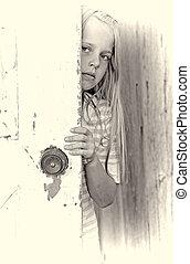 young girl behind door