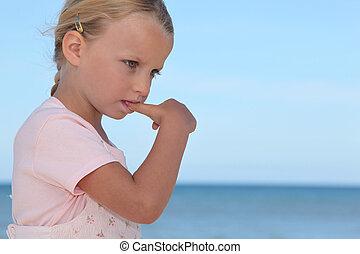 Young girl biting her thumbnail