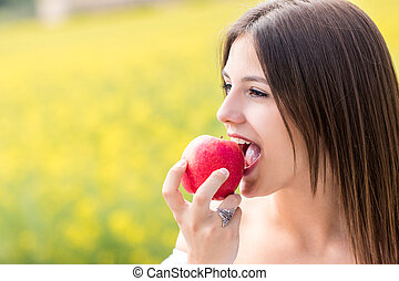 Young girl biting red apple outdoors.