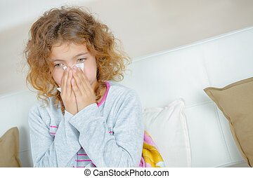 Young girl blowing nose with tissue