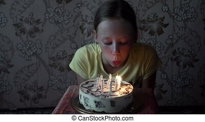 young girl blowing out birthday candles