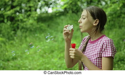 Young girl blowing soap bubbles outdoor
