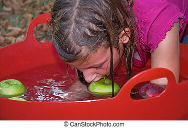 This young girl is bobbing for green apples in water in a red tub.