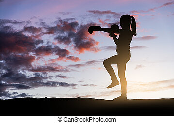 Young girl boxing at sunset.