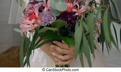 young girl bride in a wedding dress is holding a bouquet of ...