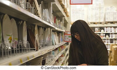 Young girl buying plates in section of dishware. Beautiful...