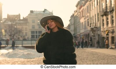 Young girl calling somebody on the phone, talking and smiling happily