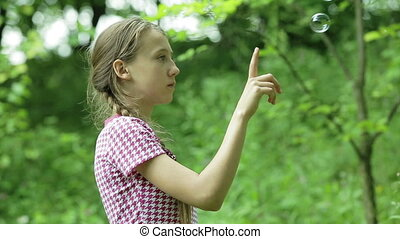 Young girl catches soap bubbles in the park