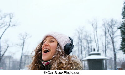Young girl catching snowflakes with the mouth in a Park with headphones closeup.