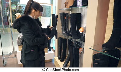 Young girl chooses in the boutique winter boots