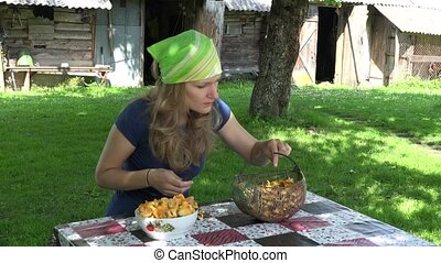 young girl clean forest chanterelle at table village yard. 4K