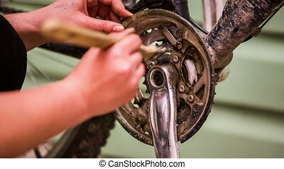 Young Girl Cleaning Bicycle Chainring With Brush - Closeup...