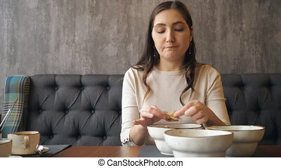 Young girl cleans and eats shrimp in a restaurant, slow...