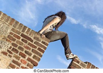 Young girl climbing on brick wall over blue sky