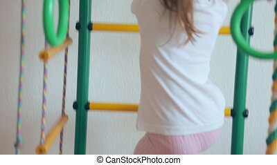 Young girl climbing up and down gymnastic complex