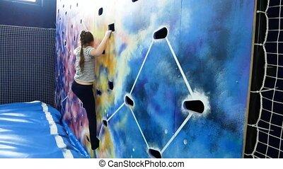 Young girl climbing up on indoors climbing wall - Young girl...