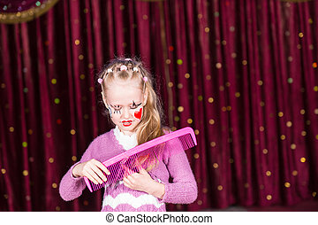 Young Girl Clown Brushing Hair with Large Comb