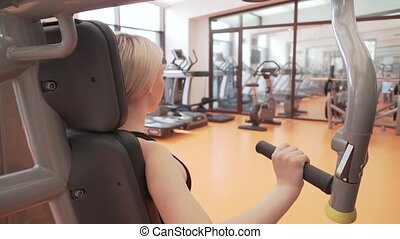 Young girl coaches muscles of hands on a simulator in gym...