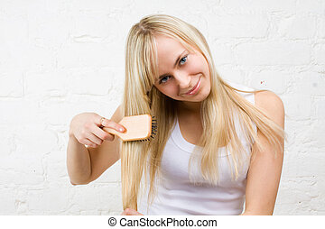 Young girl combing long blonde hair