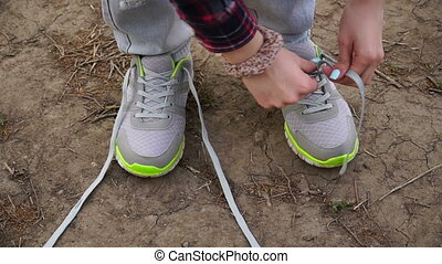 young girl commits an outdoor walk and stopped to tie her shoelaces on sneakers