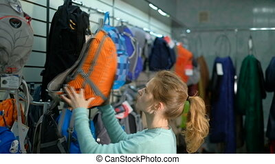 Young girl consultant in a specialty store for the tourism picks backpack. 4k