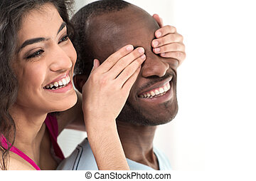 young girl covering her boyfriend eyes with both hands....