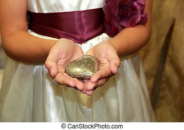 Young girl cradling heart stone