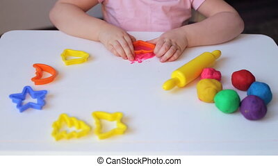 Young girl creating heart with red plasticine