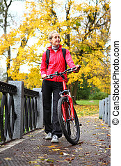 Young girl cyclist with bike on bridge in autumn park
