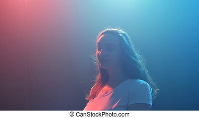 Young girl dancing in color light - smiling young girl...